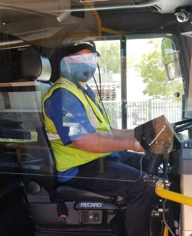 Image of bus driver behind clear protective shield