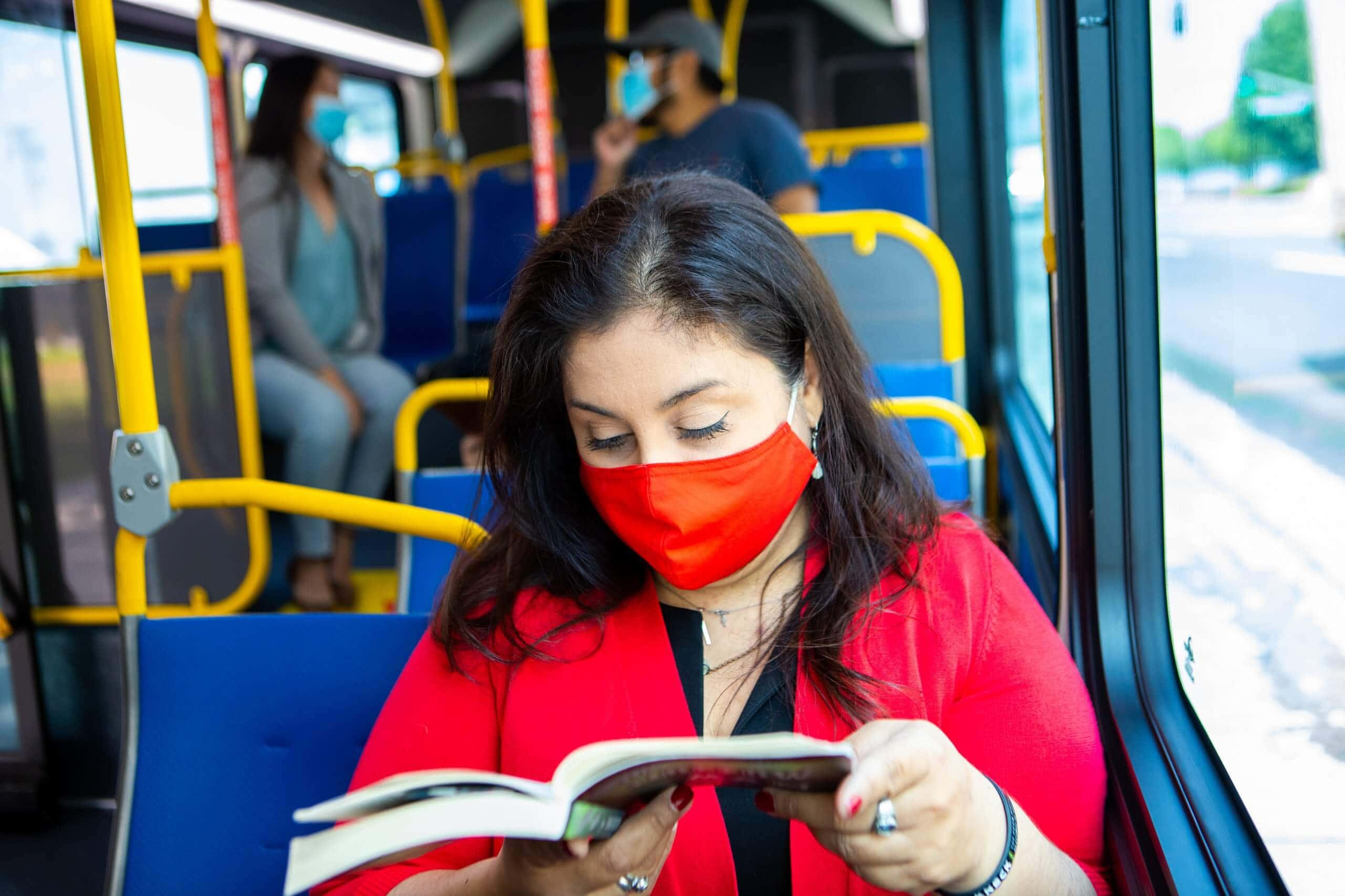 Masked passenger on bus reading book