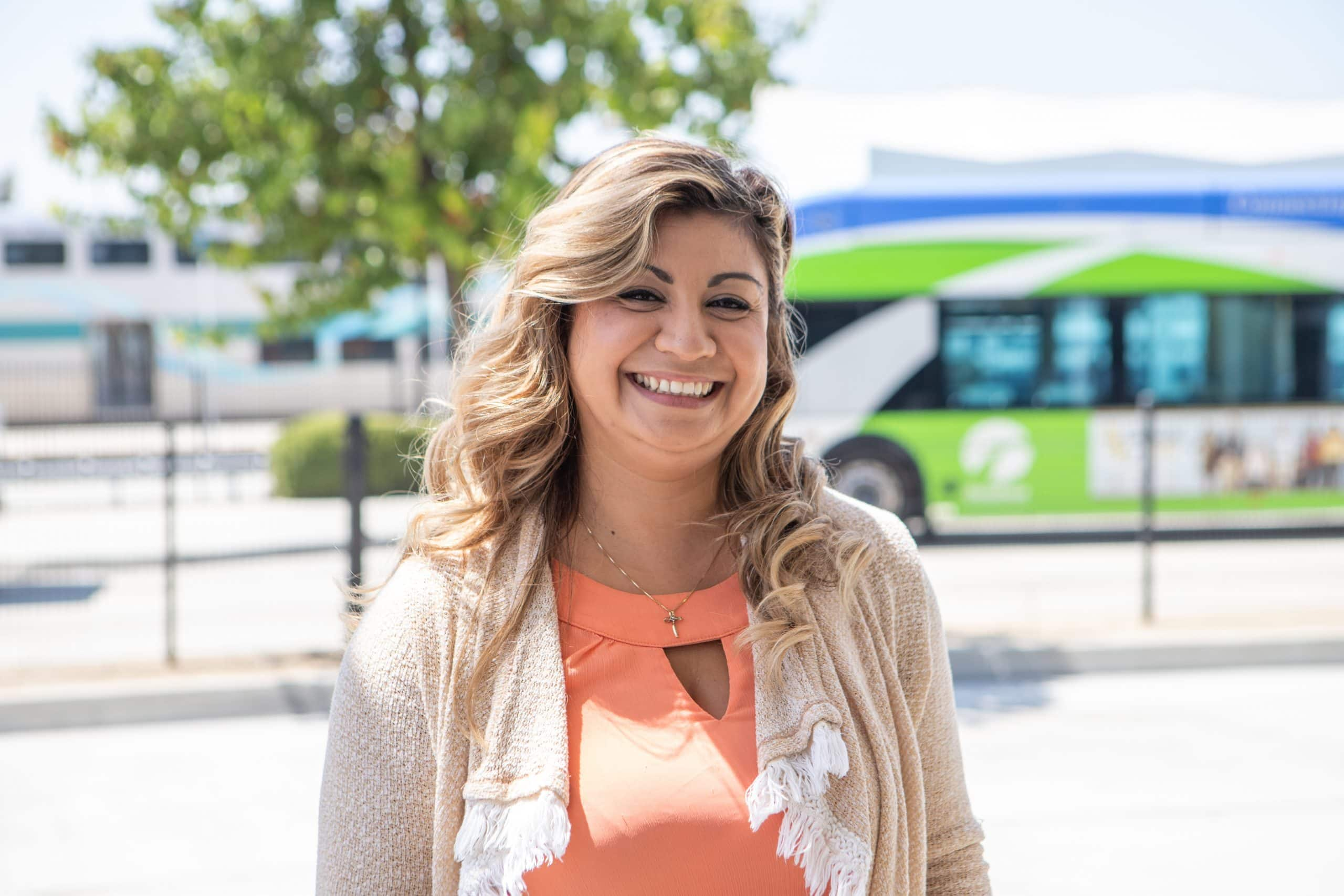smiling woman in front of bus